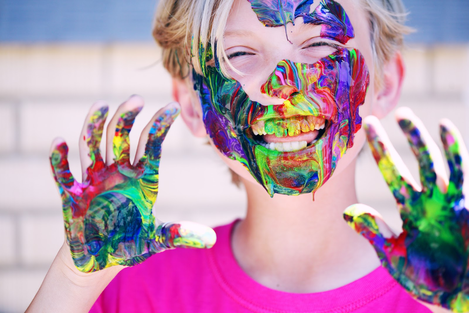 boy with hands and face covered in rainbow paint