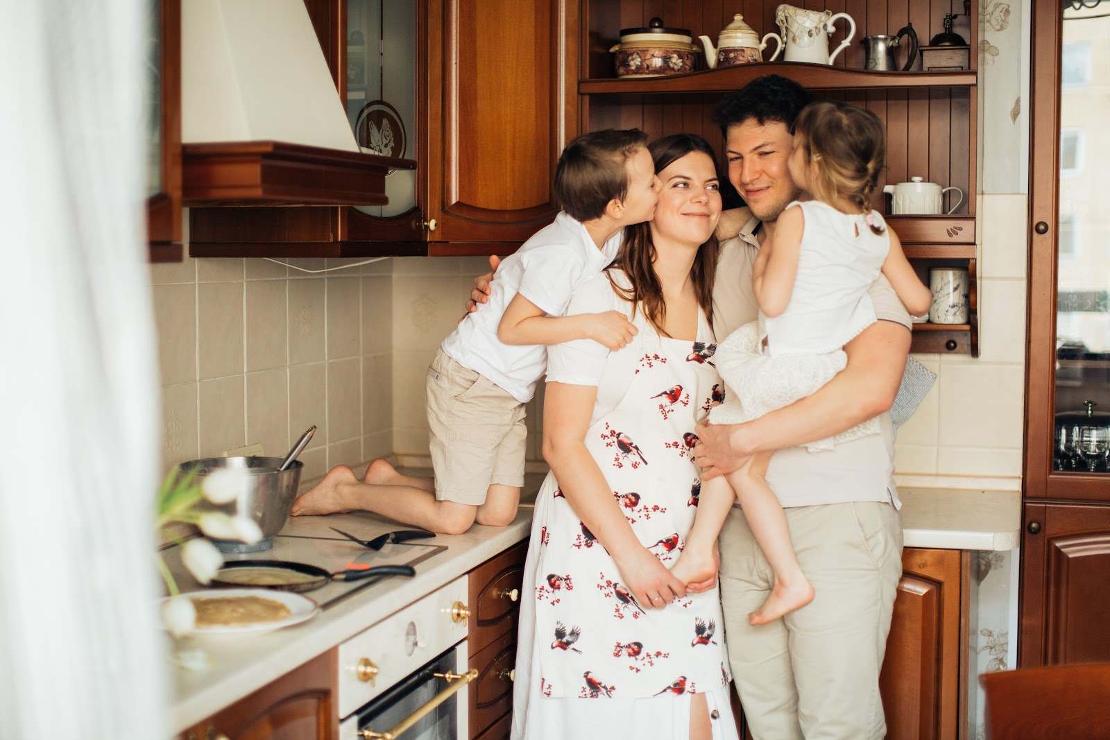 Mother, father, son and daughter gathered hugging in kitchen