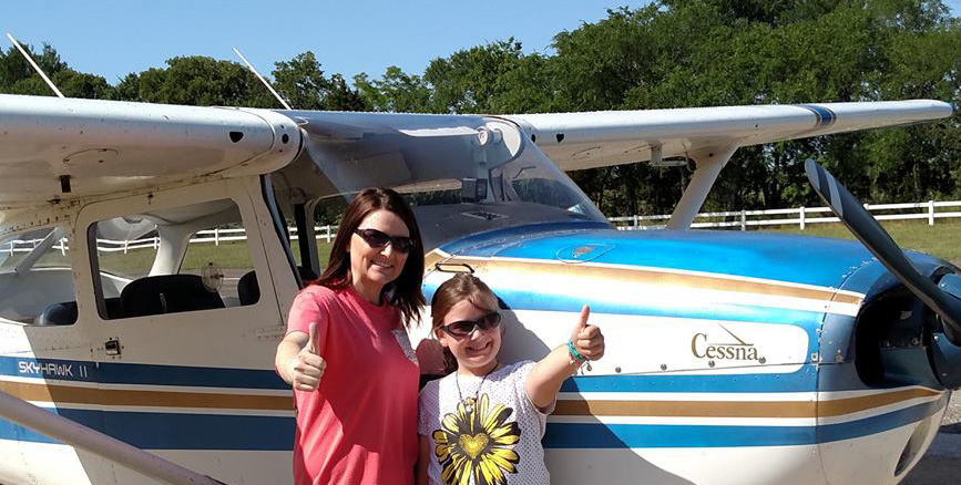 Photo of woman and daughter by a Code 1 training airplane