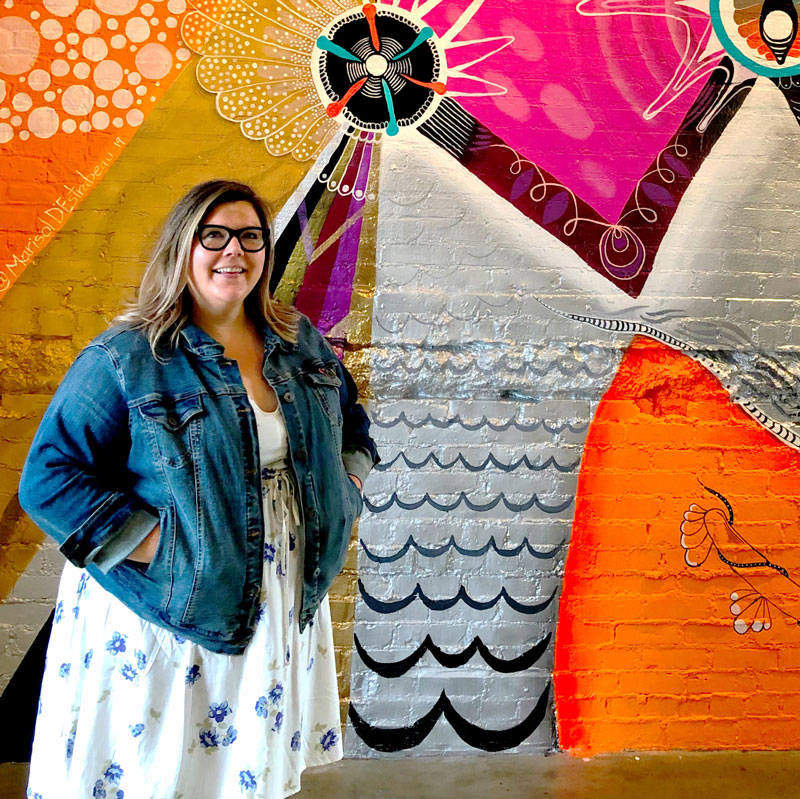 Woman standing in front of a colorful mural