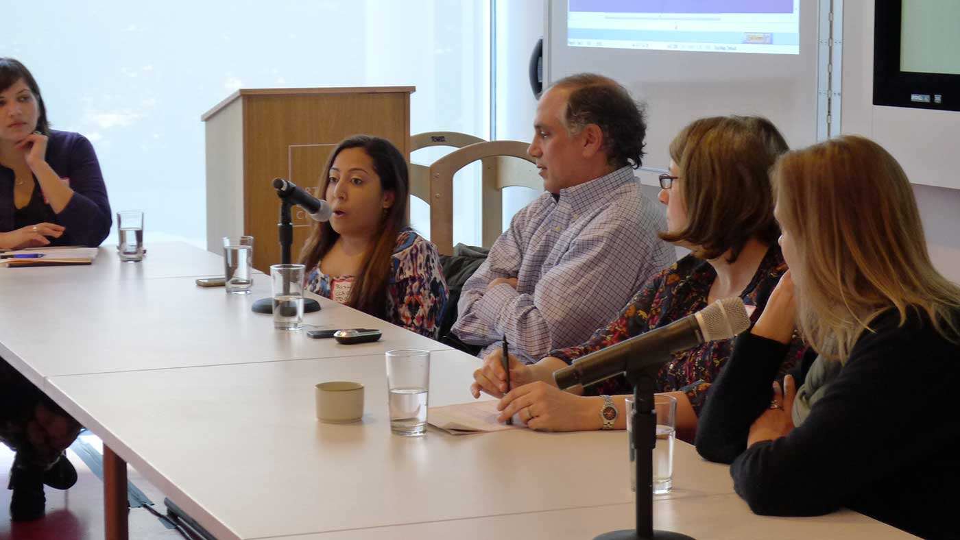 Photo of Risa Rifkind giving a presentation along with other panelists.