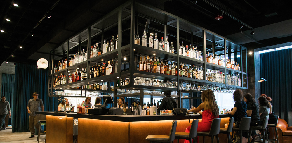 photo of Front Bar with bar in the center of the room surrounded by stools and bottles above.