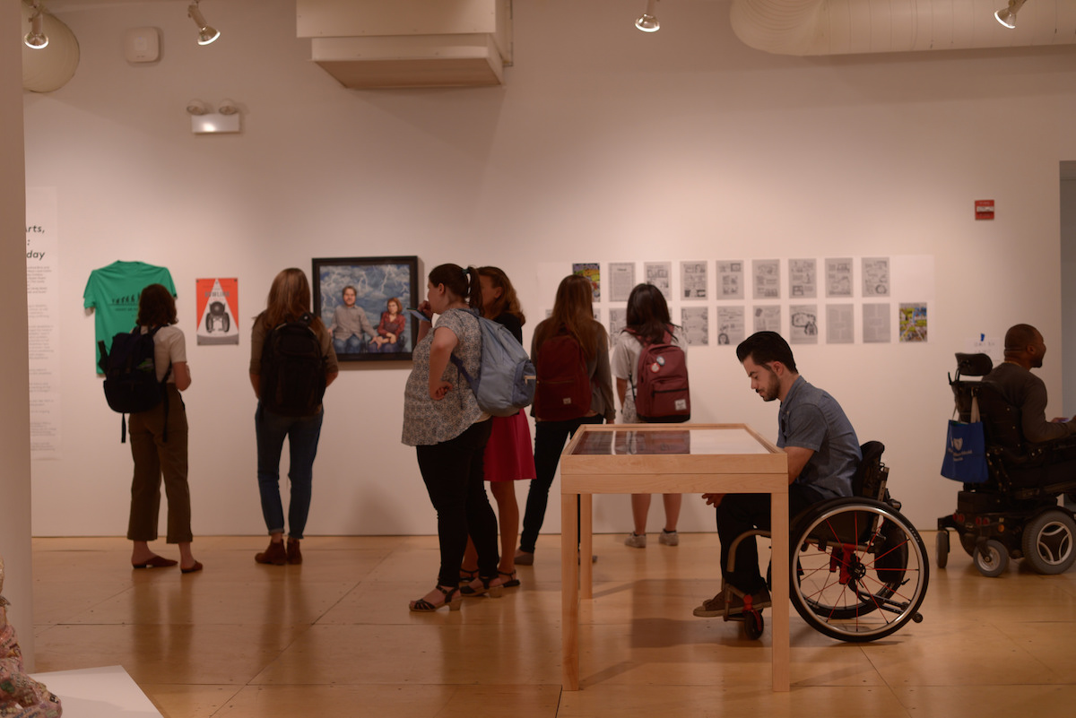 Man in a wheelchair examines art in a glass case while other museum goers look at hanging artwork on walls