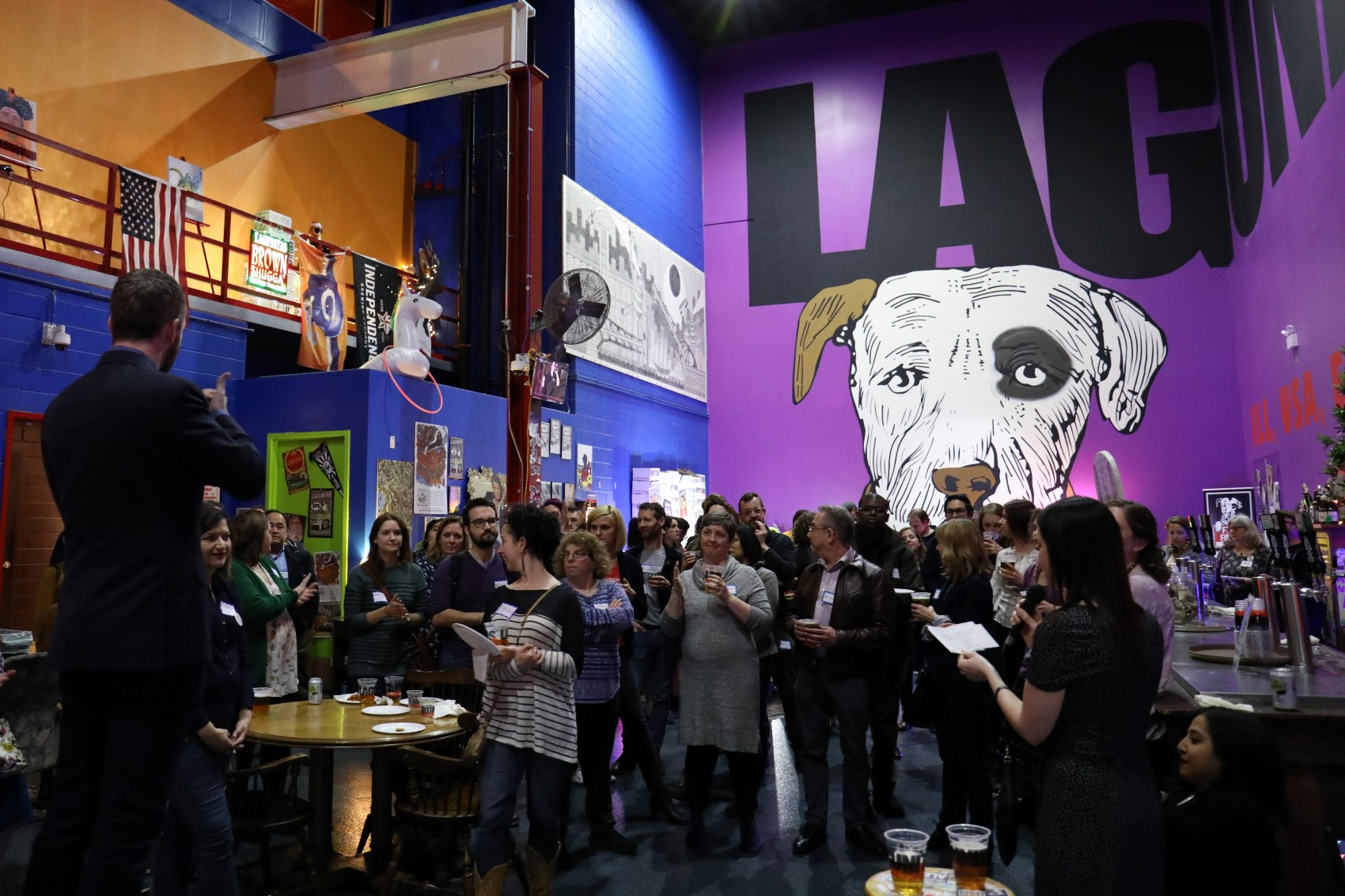 Image from 2019's Fundraiser at Lagunita's Basement. A crowd of attendees from CCAC's 2019 Fundraiser gather, drinks in hand, for remarks led by CCAC Founder Christena Gunther. In the foreground, there is a sign language interpreter elevated to Christena's left.