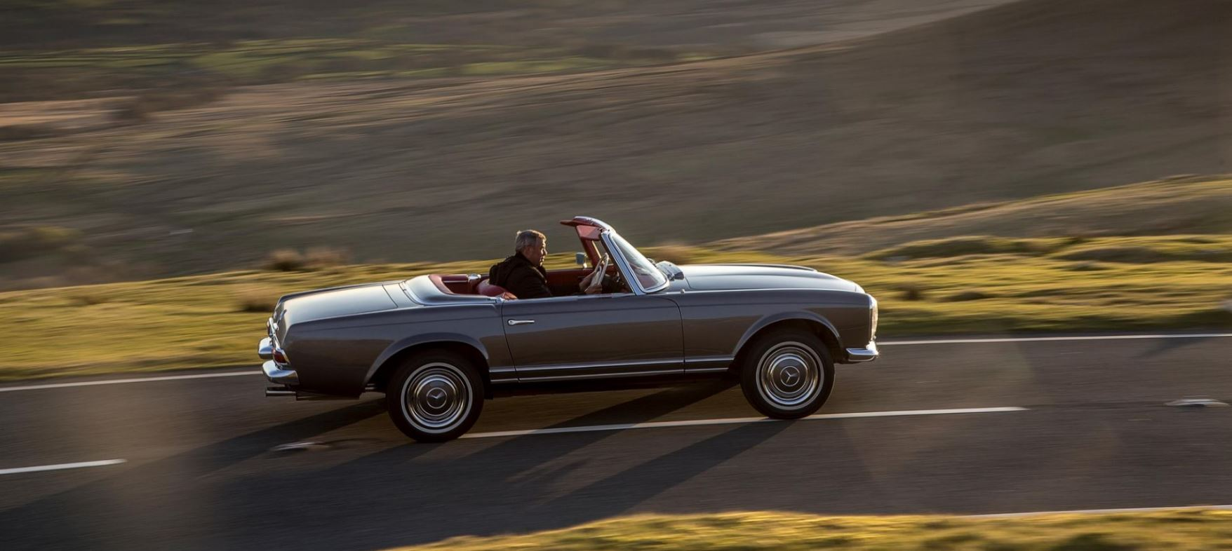 Classic 1971 Mercedes-Benz W113 280SL Pagoda Roadster in Anthracite with red interior driving in mountains in Wales