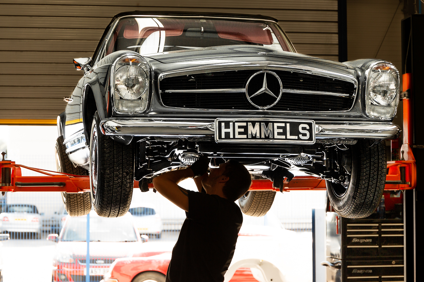 Hemmels mechanic working underneath a Mercedes-Benz 280SL Pagoda