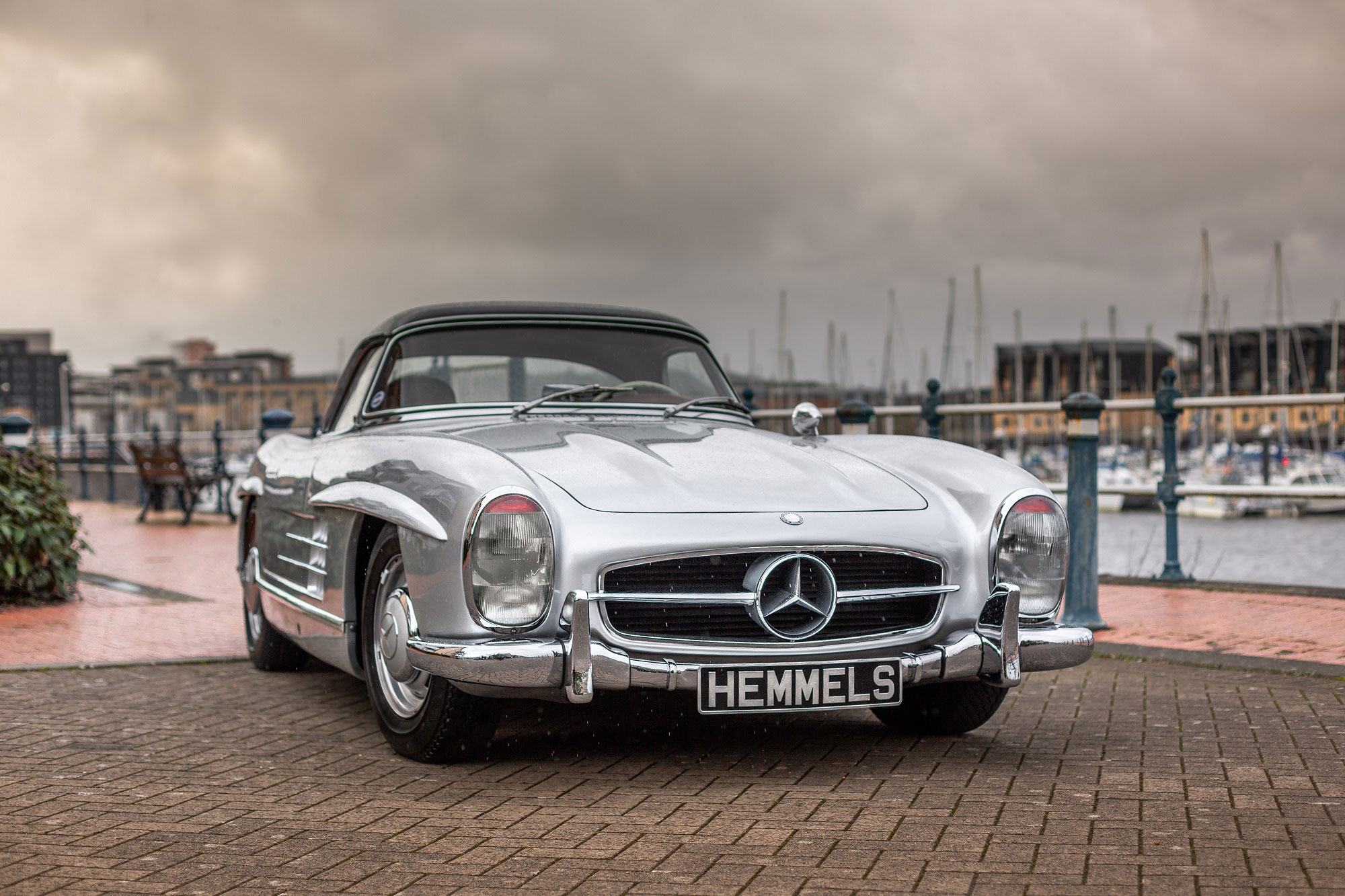 Classic Mercedes-Benz W198 300SL Roadster by marina in rain silver with red interior and black hardtop