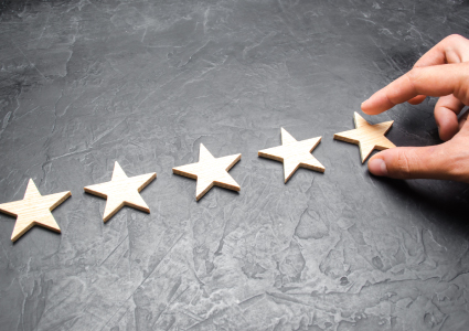 Hand putting up the 5th star in a row