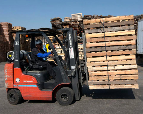 Photo of forklift carrying wood pallets