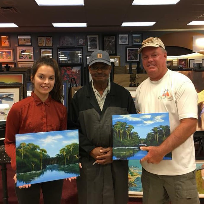 Photo of artist Curtis Arnett and two Paint the Town Citrus patrons holding their artwork from his class
