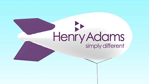 A blimp with Henry Adams branding