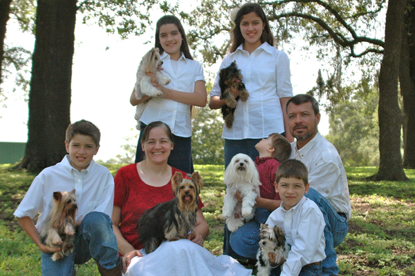 family of mother, father, two daughters and two sons, holding puppies