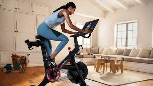 woman in work out clothes on her peloton bike