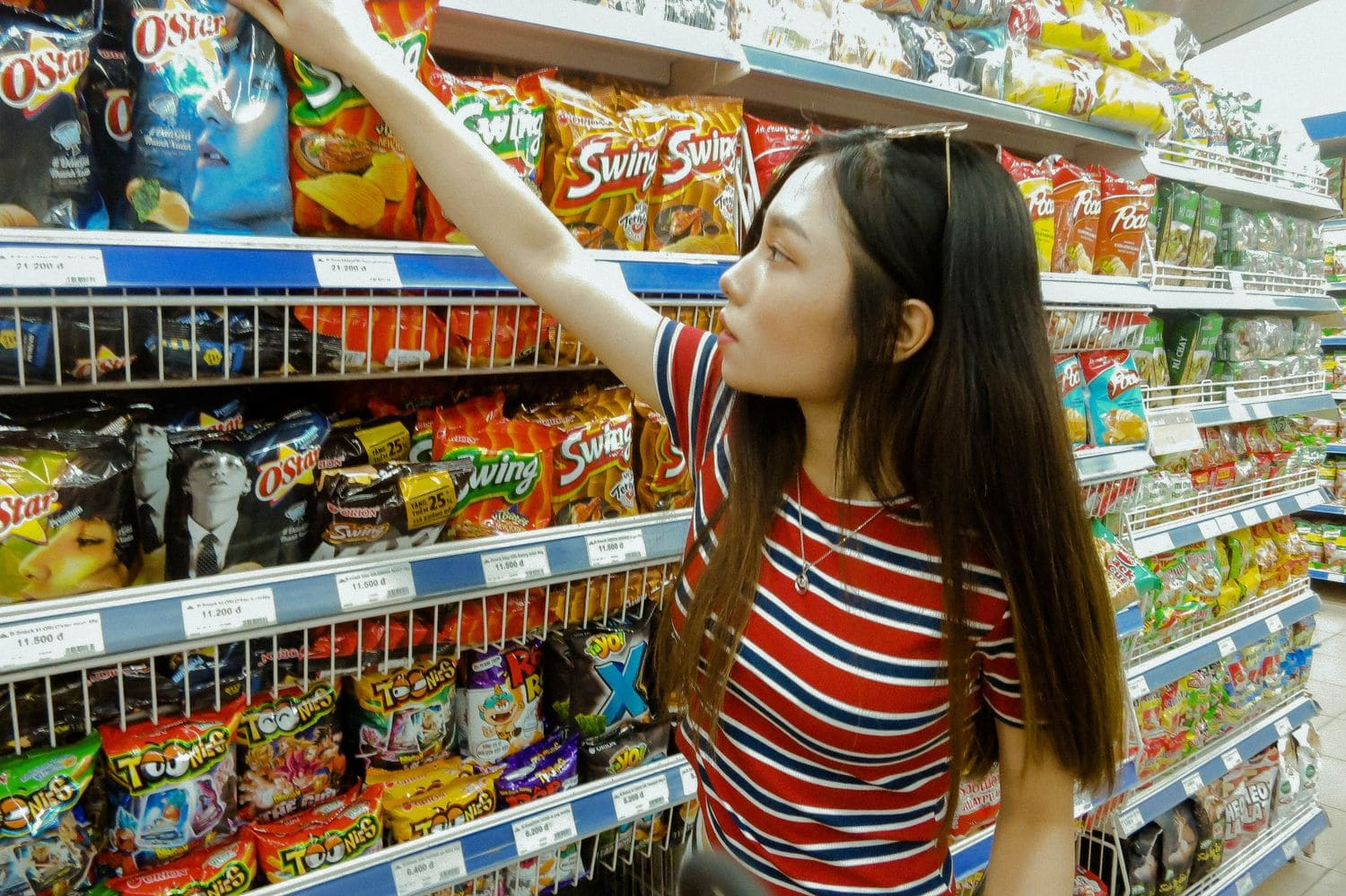 a woman in a supermarket grabbing chips