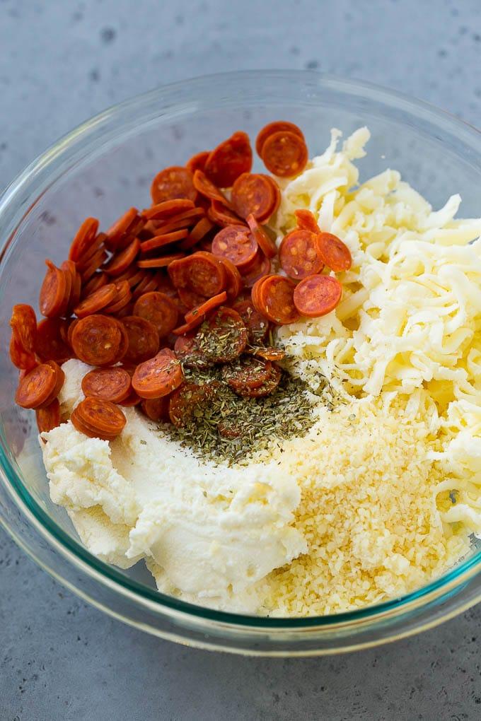 A bowl of ricotta cheese, mozzarella cheese, parmesan cheese, mini pepperoni and Italian seasoning.