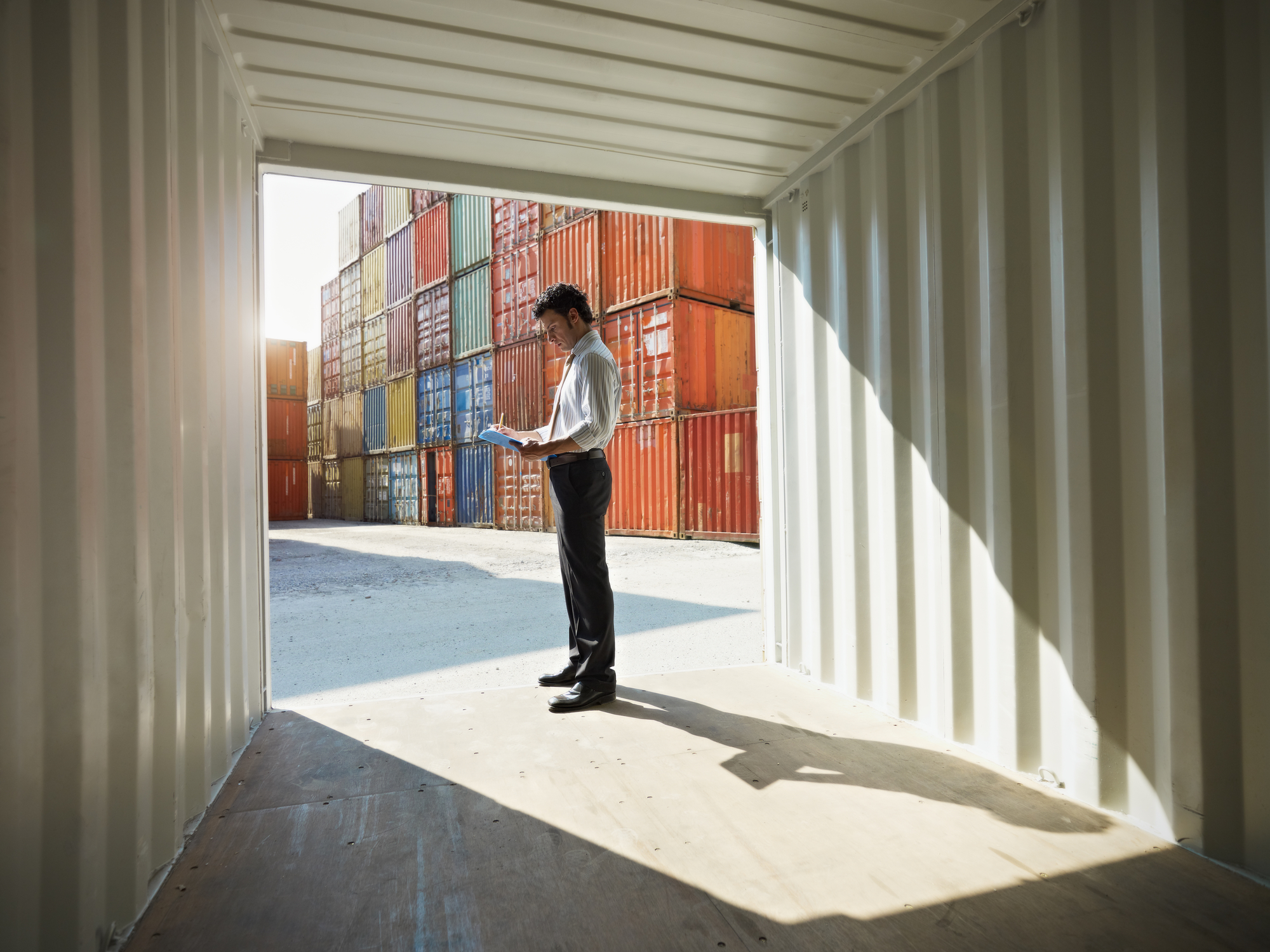 Man does paperwork at shipping container