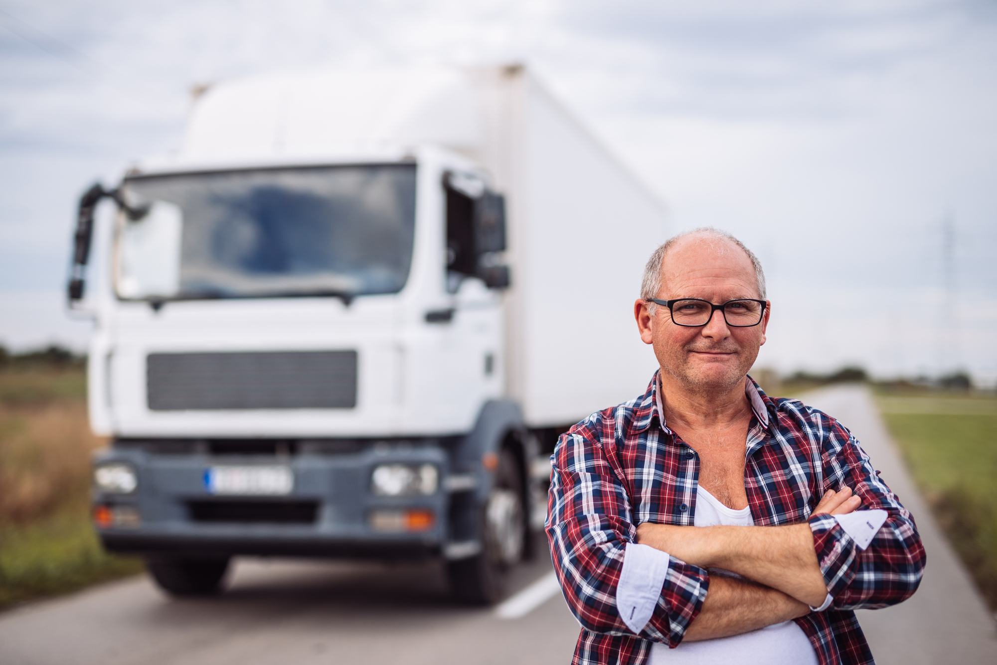 A truck driver stands in front of his truck