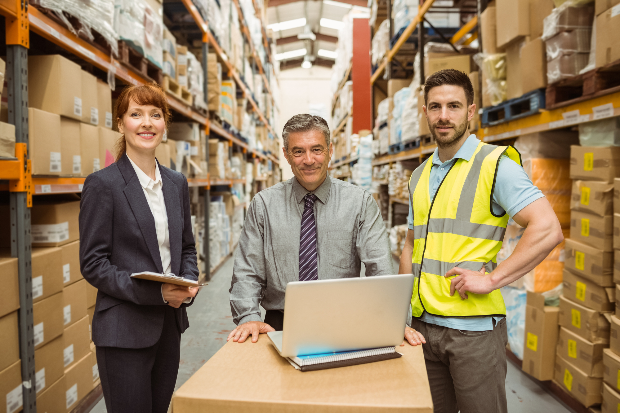 Three logistics professionals in a warehouse