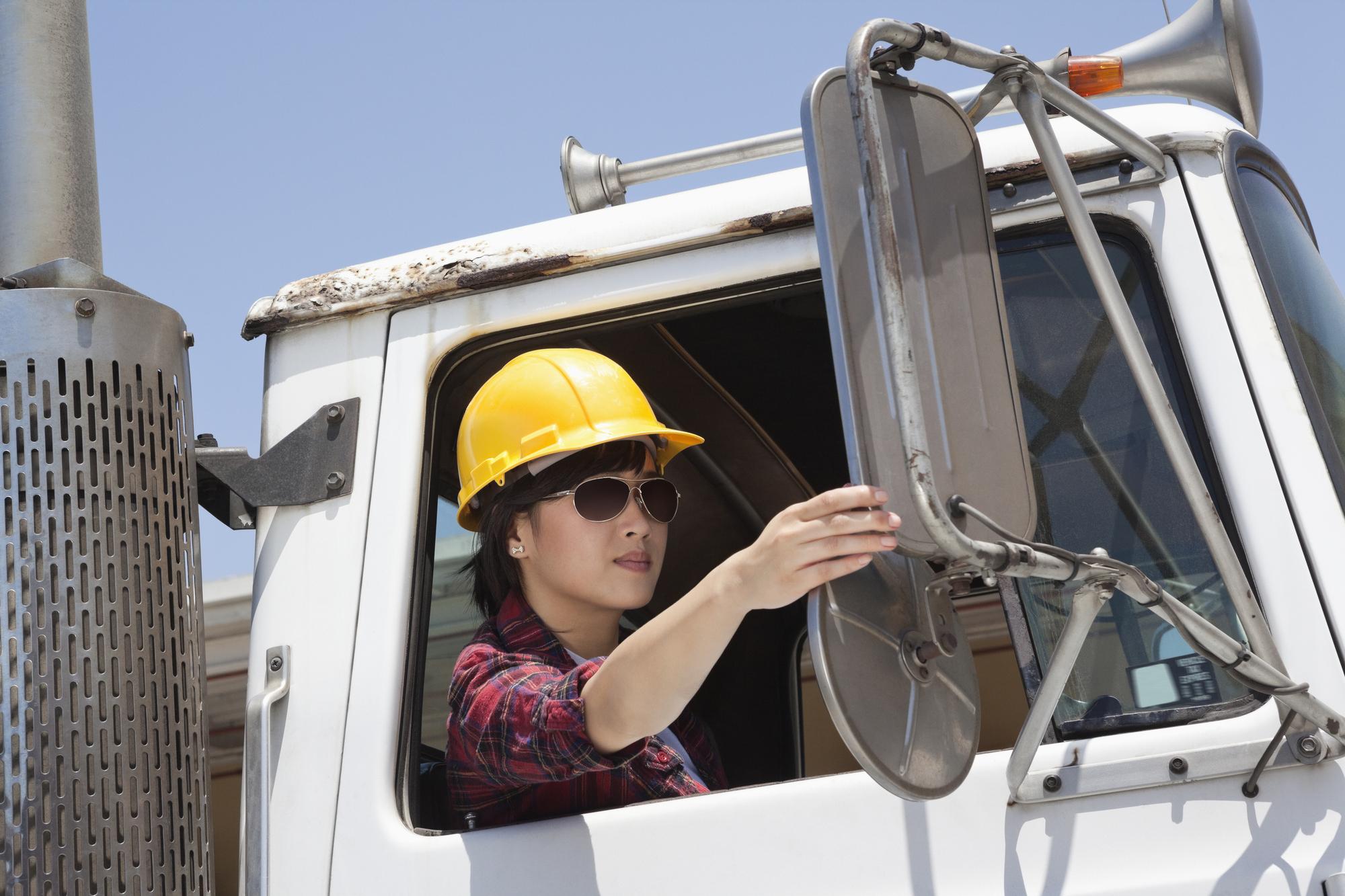A woman drives a semi truck