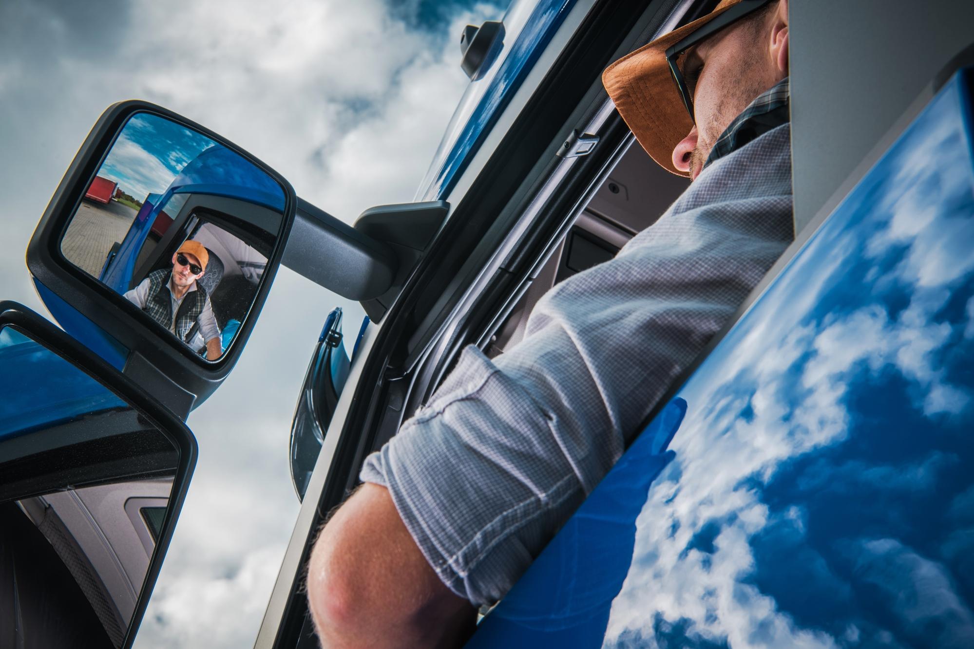Trucker looks in the side mirror