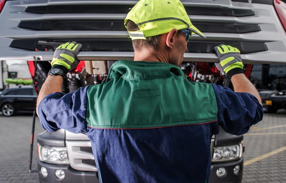 A mechanic inspects under the hood of a truck