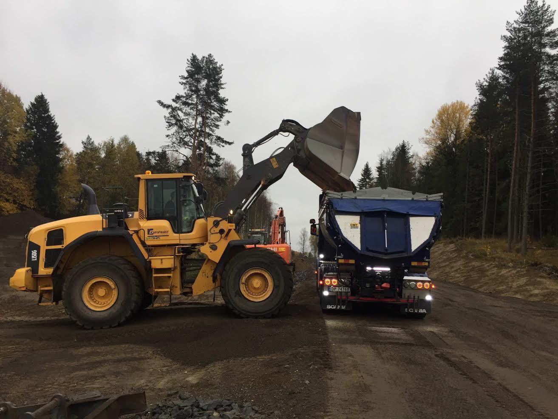 Lastebil som lastes av stor hjullaster
