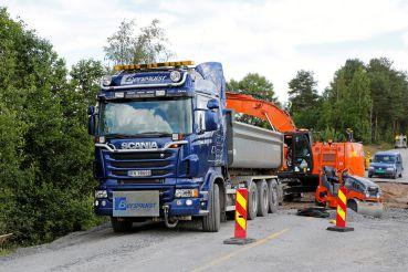 Lastebil med graver, vals og firmabil