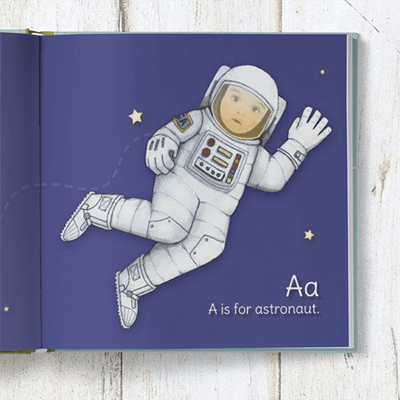 A is for Astronaut page of the personalized ABC book.  An astronaut is floating in space against a blue background, with the child's face inserted into the astronaut helmet