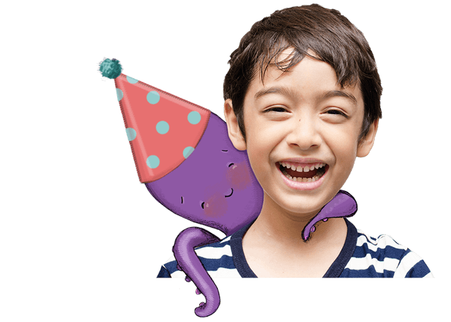 Happy, smiling boy with an illustrated purple octopus hugging his neck, against a blue background with gift boxes and birthday candles