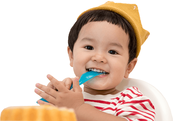 Happy toddler boy with a spoon in his mouth, eating cake, against a blue background with gift boxes and birthday candles