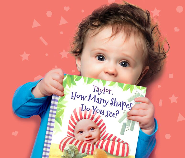 Photo of a toddler girl holding her personalized copy of How Many Shapes Do You See?.  Her name is on the book cover as is her face.
