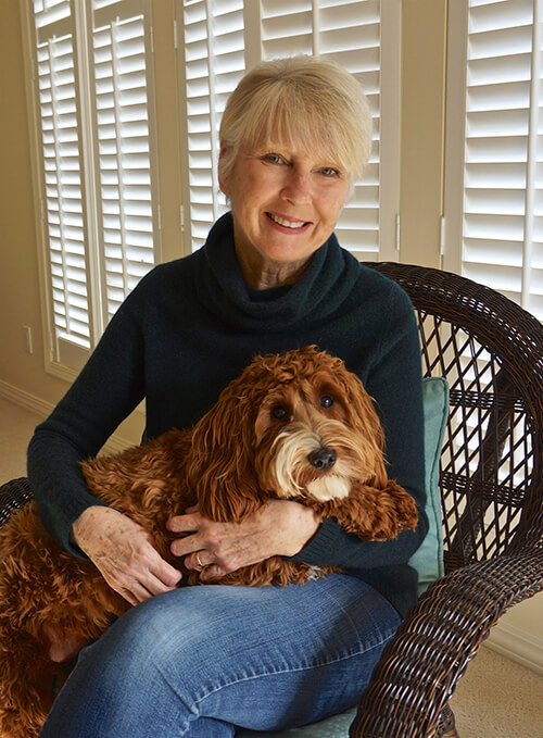 Photograph of Stephanie Shaw, author of How Many Shapes Do You See?, sitting in a chair holding a dog.