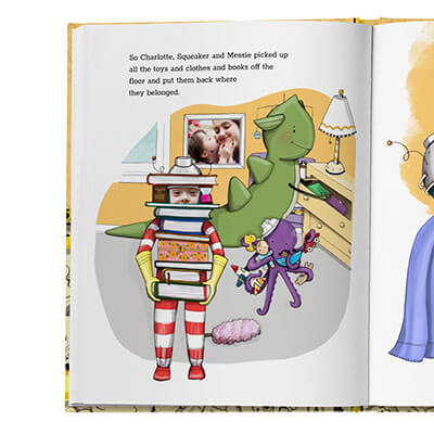 Sample book page showing child cleaning up room. Child is carrying stack of books while other characters (a monster and octopus) are helping to clean in background. Family photo appears as wall art.  The child's face and family photo are actual photos, the rest of the page is illustrated.