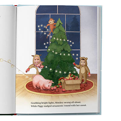 A festive scene of the main character dressed as a reindeer, hanging Christmas decorations with animal friends.  The main character's sibling, also dressed as a reindeer, is also shown. Page is illustrated with the exception of the children's faces, which utilize actual photos.