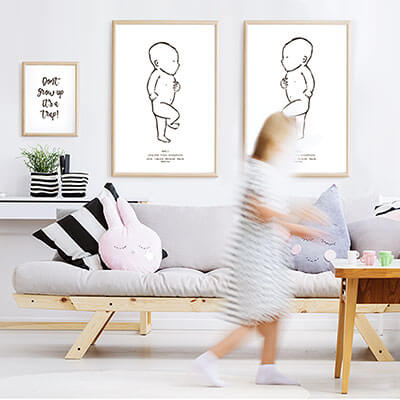 Lifestyle shot of two portrait Newborn Posters in a playroom.