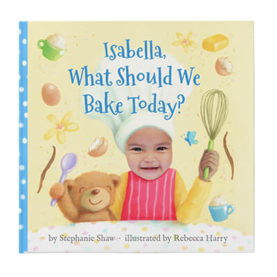 Personalized birthday book cover featuring a young girl named Isabella wearing a chef's hat and holding a whisk in one hand, and a teddy bear in her other arm.