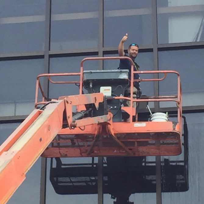the windows of this high rise building being meticulously cleaned