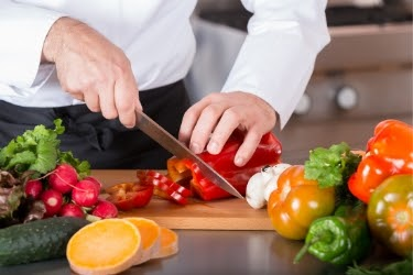 person chopping vegetables at a cutting board