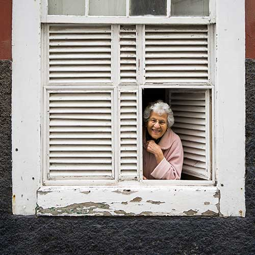 smiling elderly woman looking out the window