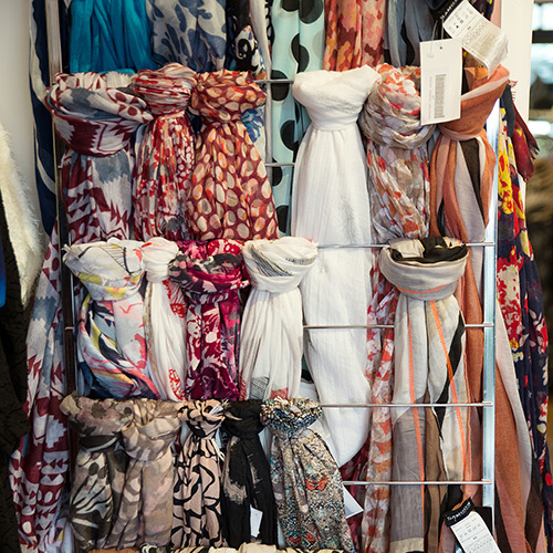 photo of one of the accessory rails in the shop, featuring scarves