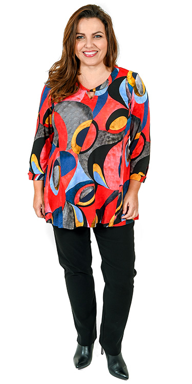 This model is wearing a bright abstract print top with keyhole neck feature teamed with Mona Lisa narrow stretch trousers in black from plus size boutique Bakou in West Wimbledon