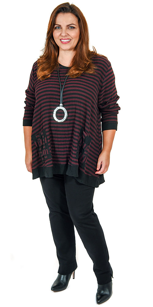 This image shows a striped tunic from Coom or Sinne in merlot/black stripe teamed with Robell black pull on stretch jeans