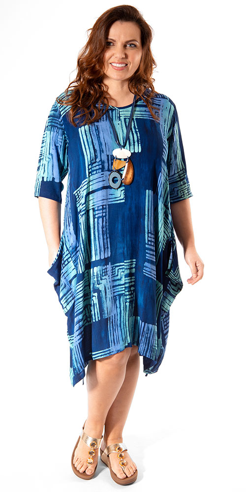 This image shows a model wearing a loose dress, perfect for holidays, by Angel Circle teamed with a chunky necklace. Available in plus sizes from Bakou in West Wimbledon.