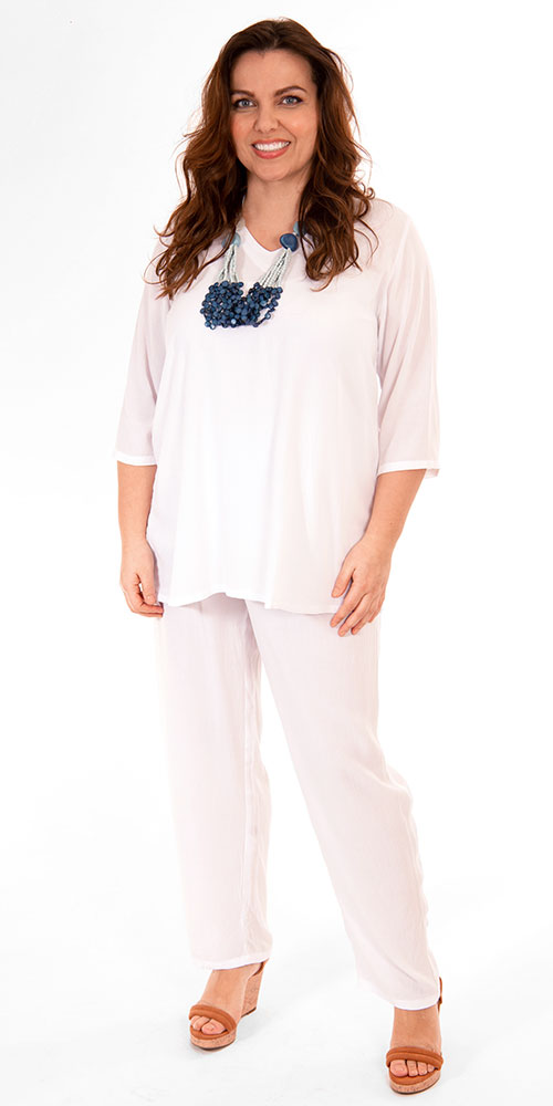 This image shows a model wearing a v neck crinkle viscose white t-shirt with matching trousers from Angel Circle. Sizes 14-30 from Bakou.