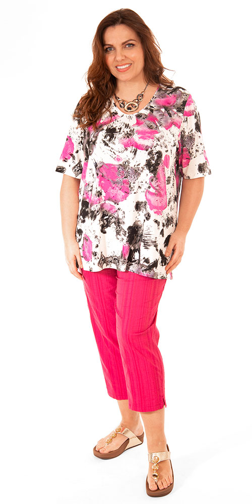 This image shows a model wearing a pretty pink patterned t-shirt teamed with Wash & Go crop trousers from K J Brand. Plus sizes from Bakou.