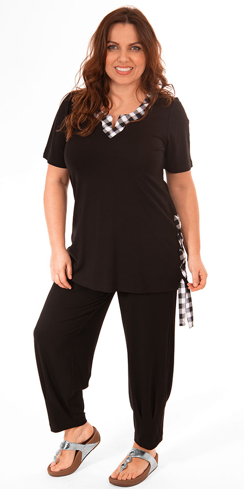 This image shows a model wearing a See You t-shirt with check detail on the neck and check ribbon detail on the side paired with Q'neel harem trousers in black.