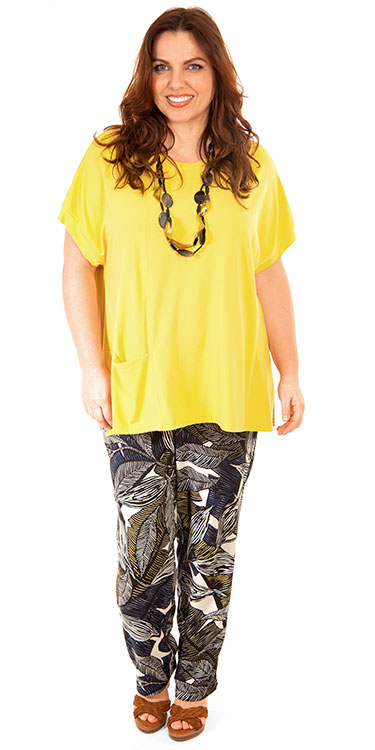 This model is wearing a buttery yellow loose fit t-shirt from Q'neel teamed with leaf print trousers