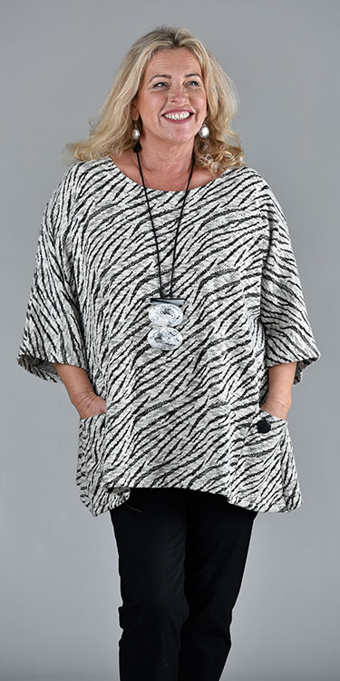 This model is wearing a Kaden wide cut abstract animal print sweater with pocket and button detail by Kasbah Clothing.