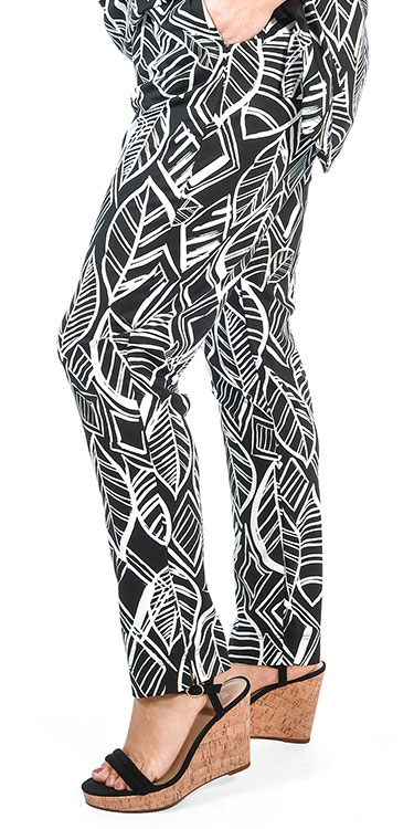 This model is wearing Sempre Piu leaf print jersey black and white trousers