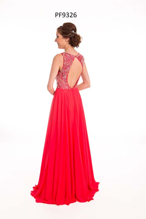 Prom girl wearing a strawberry red chiffon gown with silver beaded top, keyhole back and full skirt